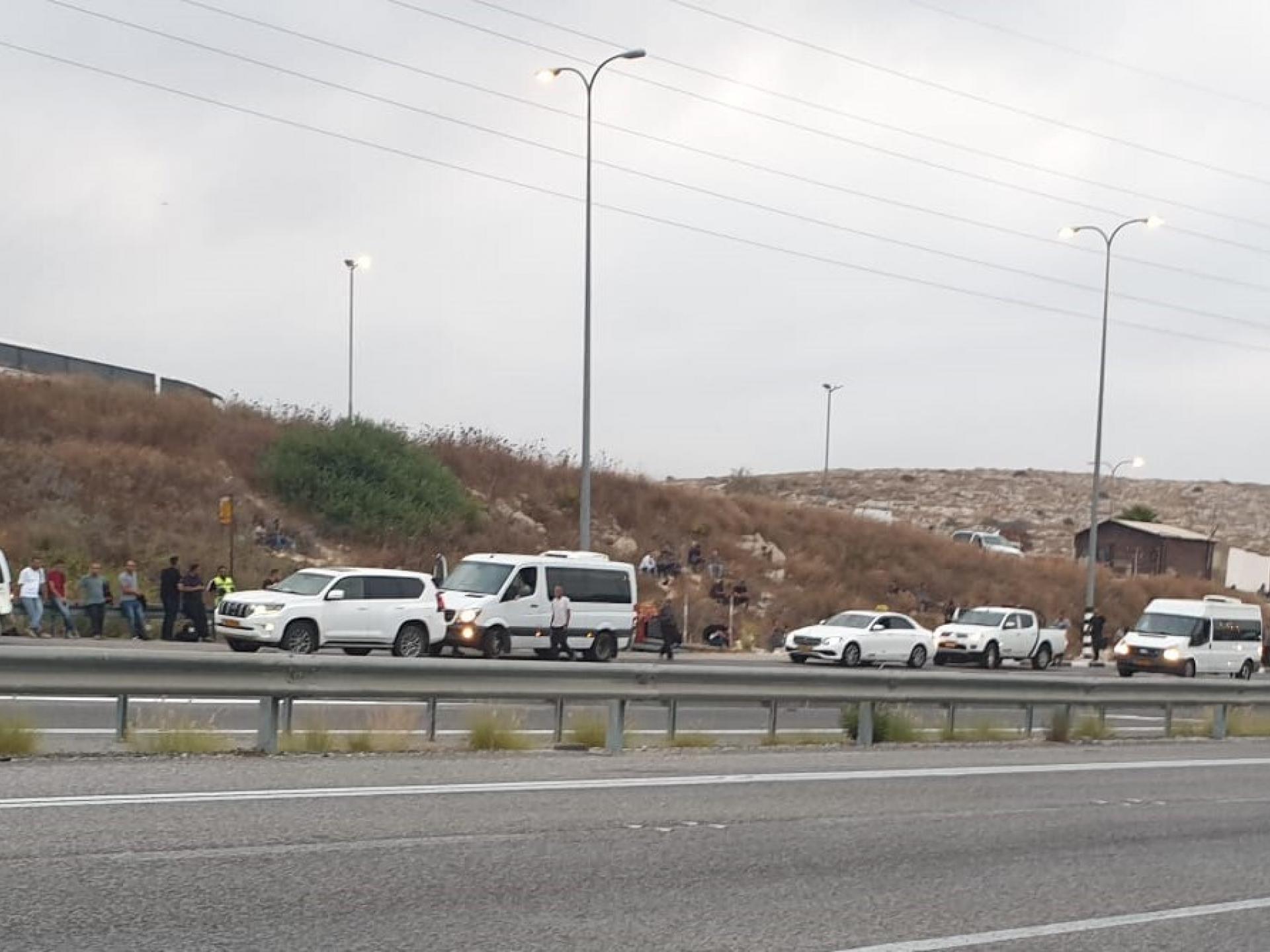 מכוניות מחכות לאסוף פועלים בצד הכביש