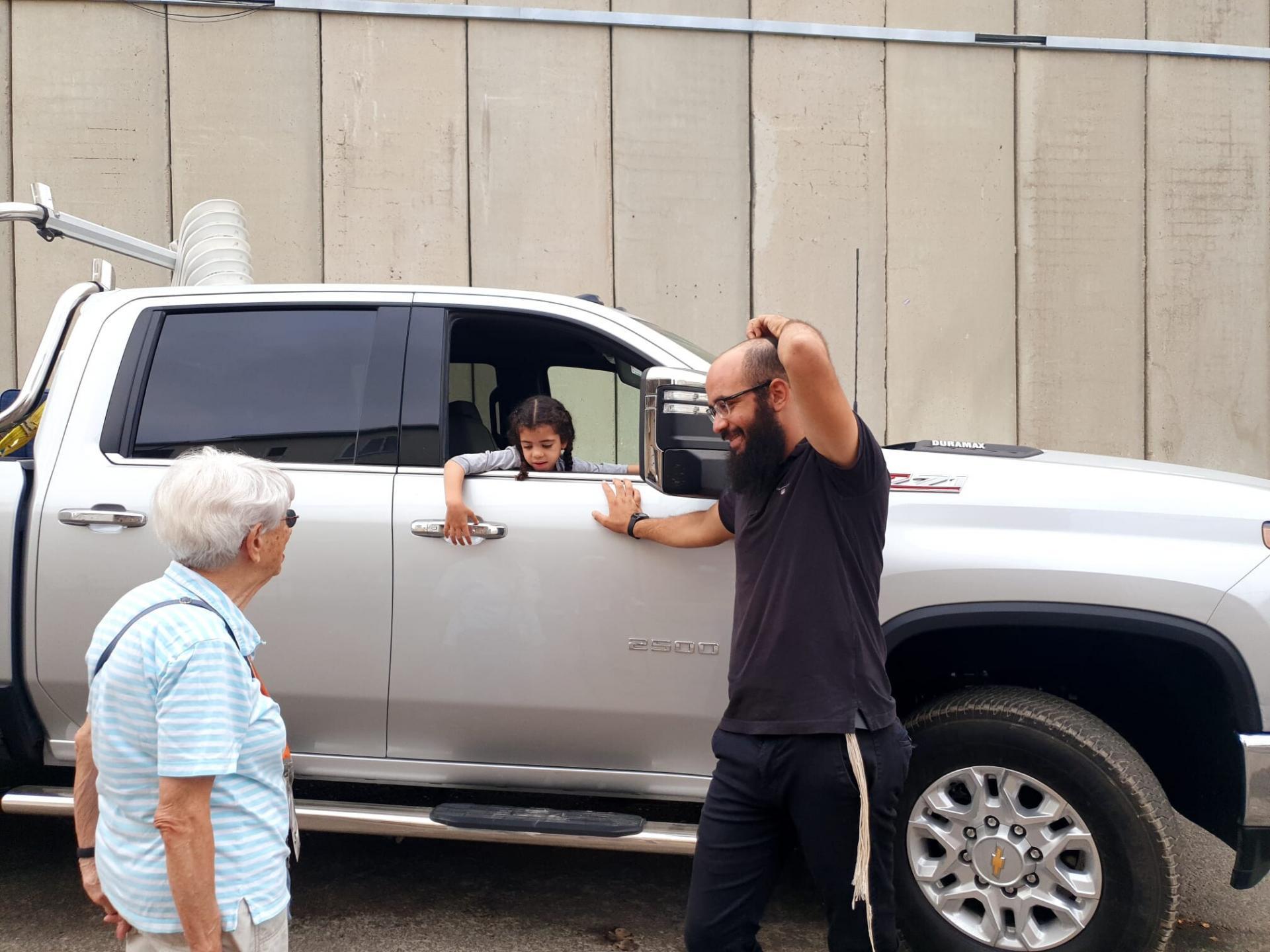 אישה משוחחת עם גבר ובתו היושבת במכונית