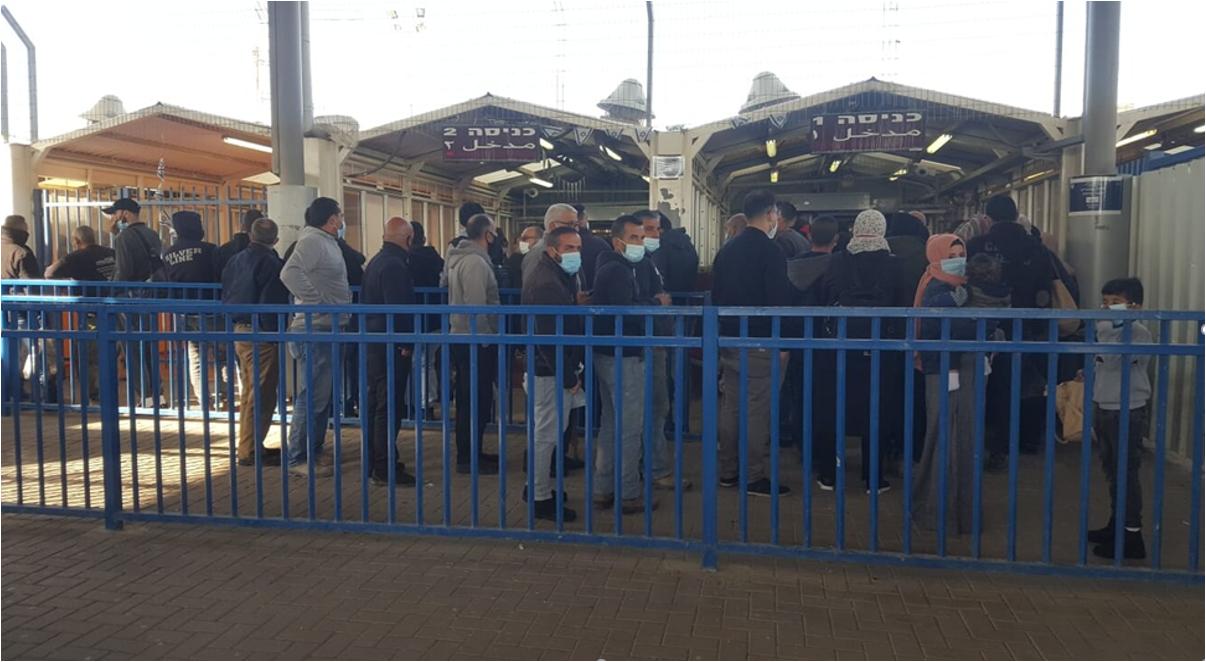 אנשים עומדים בין סורגים בכניסה למחסום